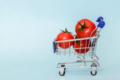 Grocery cart with cherry tomatoes standing on blue background. Place for text royalty free stock images