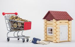 Grocery cart filled with coins, a keychain and a house for children royalty free stock photos