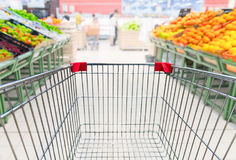Grocery cart in fruit department of supermarket stock image
