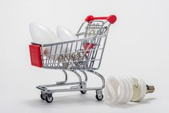 In the grocery cart are LED bulbs, next is an energy-saving light bulb royalty free stock photos