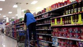 Grocery clerk stocking coffee