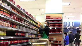 Grocery clerk stocking food for sale stock video footage