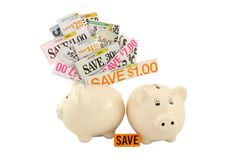 Grocery Coupons In A Piggy Bank. Two small piggy banks isolated on a white background; one overflowing with money saving grocery coupons Stock Photography