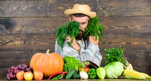 Grocery shop concept. Buy fresh homegrown vegetables. Excellent quality vegetables. Man with beard proud of his harvest. Vegetables wooden background. Farmer stock photography