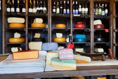 Grocery shop interior. Shelves and counter with cheese. Grocery shop interior. Cheese wheels arranged on wooden shelves, coloured cheese and wrapping paper on royalty free stock photos