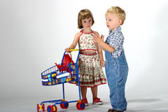 Grocery shopping. Toddler boy and girl playing grocery shopping with a toy shopping cart and toy groceries royalty free stock image