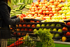 Grocery shopping. A woman shopping for apples at a grocery store or supermarket Stock Photography