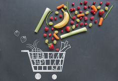 Grocery shopping cart concept. Grocery shopping cart sketched on a chalkboard combined with fruits and vegetables Royalty Free Stock Photo