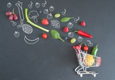 Grocery shopping cart concept. Grocery shopping cart filled with fruits and vegetables and sketches on a chalkboard Stock Photos