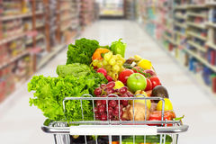 Grocery shopping cart with vegetables. Grocery shopping cart with vegetables and fruits on supermarket background royalty free stock images