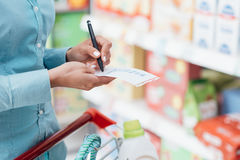 Grocery shopping list. Woman doing grocery shopping at the supermarket, she is pushing a cart and checking items on a list Stock Photos