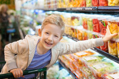 Grocery shopping. Smiling positive boy grocery shopping at the supermarket sitting in the cart helping his mother Stock Photography