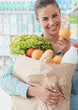 Grocery shopping. Smiling young woman doing grocery shopping at the supermarket, she is holding a bag with fresh vegetables, bread and milk Stock Photo