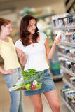 Grocery shopping store - Brown hair young woman. In a supermarket Royalty Free Stock Image