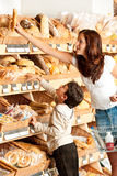Grocery shopping store - Young woman with child Royalty Free Stock Image