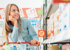 Grocery shopping at the supermarket. Attractive happy woman at the supermarket, she is doing grocery shopping and leaning on the cart Royalty Free Stock Image