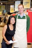 Grocery Stoer Owner With Customer. A male grocery store owner together with a customer Stock Photo