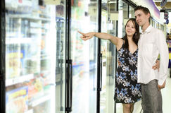 Grocery store. Youg couple looking at food near freezer in grocery store Stock Photography