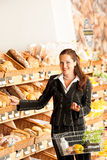 Grocery store: Business woman choosing bread Stock Image