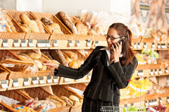 Grocery store: Business woman holding mobile Royalty Free Stock Image
