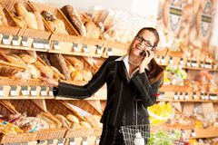 Grocery store: Business woman with mobile phone Royalty Free Stock Photo