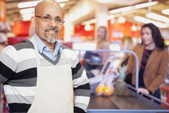 Grocery Store Cashier Standing At Checkout Counter. Portrait of a grocery store cashier standing at checkout counter with customers in the background stock photo