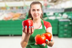 Grocery store employee presenting red, tomatoes royalty free stock images