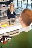 Grocery Store Flirt. A woman flirting with a man in a grocery store stock image