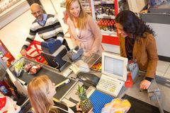 Grocery Store Line. High angle view of cashier with a line of people at the check-out counter royalty free stock image
