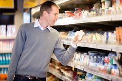 Grocery Store Man. A man buying cheese and comparing prices in a grocery store stock image