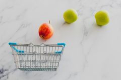 Grocery store mini shopping basket with one single red apple amo. Ng other green ones, concept of picking the best produce royalty free stock photo