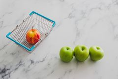 Grocery store mini shopping basket with one single red apple amo. Ng other green ones, concept of picking the best produce royalty free stock images