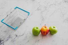 Grocery store mini shopping basket with one single red apple amo. Ng other green ones, concept of picking the best produce stock photo