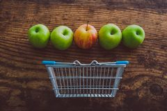 Grocery store mini shopping basket with one single red apple amo. Ng other green ones on wooden table, concept of picking the best produce royalty free stock image