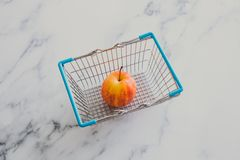 Grocery store mini shopping basket with one single red apple. And marble surface background, concept of healthy diet stock photography