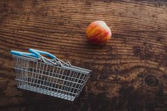 Grocery store mini shopping basket with one single red apple and. Wooden surface background, concept of healthy diet stock images