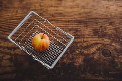 Grocery store mini shopping basket with one single red apple and. Wooden surface background, concept of healthy diet stock image