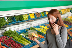 Grocery store - Red hair woman with mobile phone Royalty Free Stock Images