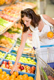 Grocery store - smiling woman choose fruit Royalty Free Stock Images