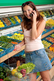 Grocery store - Smiling woman with mobile phone Royalty Free Stock Photography