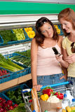 Grocery store - Two women with mobile phone Stock Photography