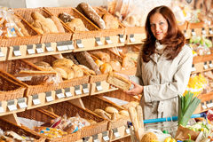 Grocery store: Young woman choosing bread Royalty Free Stock Photo