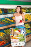 Grocery store - Young woman choosing pepper Royalty Free Stock Image