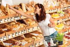 Grocery store: Young woman holding shopping basket Royalty Free Stock Photography