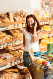 Grocery store: Young woman with mobile phone Stock Image