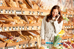 Grocery store: Young woman with mobile phone Royalty Free Stock Image