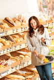 Grocery store: Young woman with shopping basket Royalty Free Stock Images