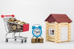 Grocery trolley filled with coins, desk clock and children`s house royalty free stock photos