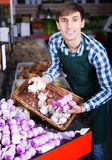 Grocery worker selling fresh garlic Stock Photography