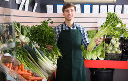 Grocery worker selling vegetables Royalty Free Stock Photos